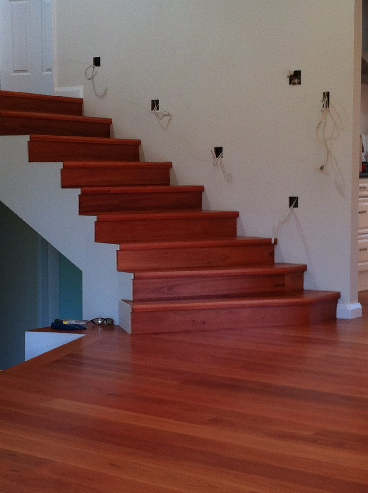 Solid hardwood Grey Gum treads and risers wrapped to concrete formed staircase with matching solid timber flooring over concrete slab supplied and installed by Timber Floors Pty Ltd