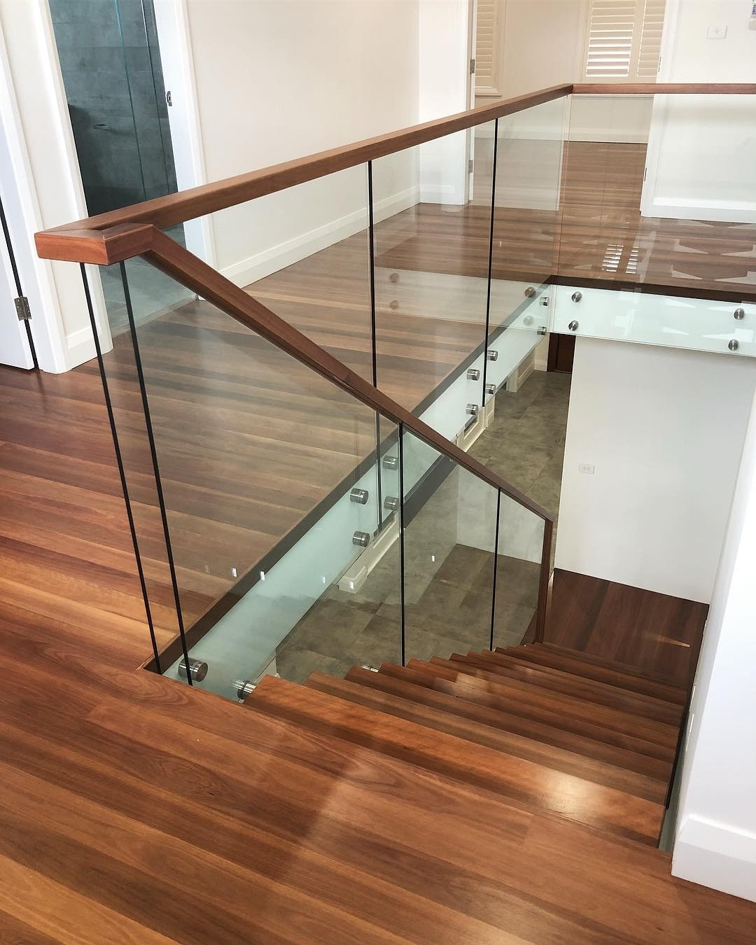 Designer Staircase Monostringer steel spine staircase with solid Australian Hardwood tread, glass Baluster and Hardwood handmade handrail supplied and installed by Timber Floors Pty Ltd