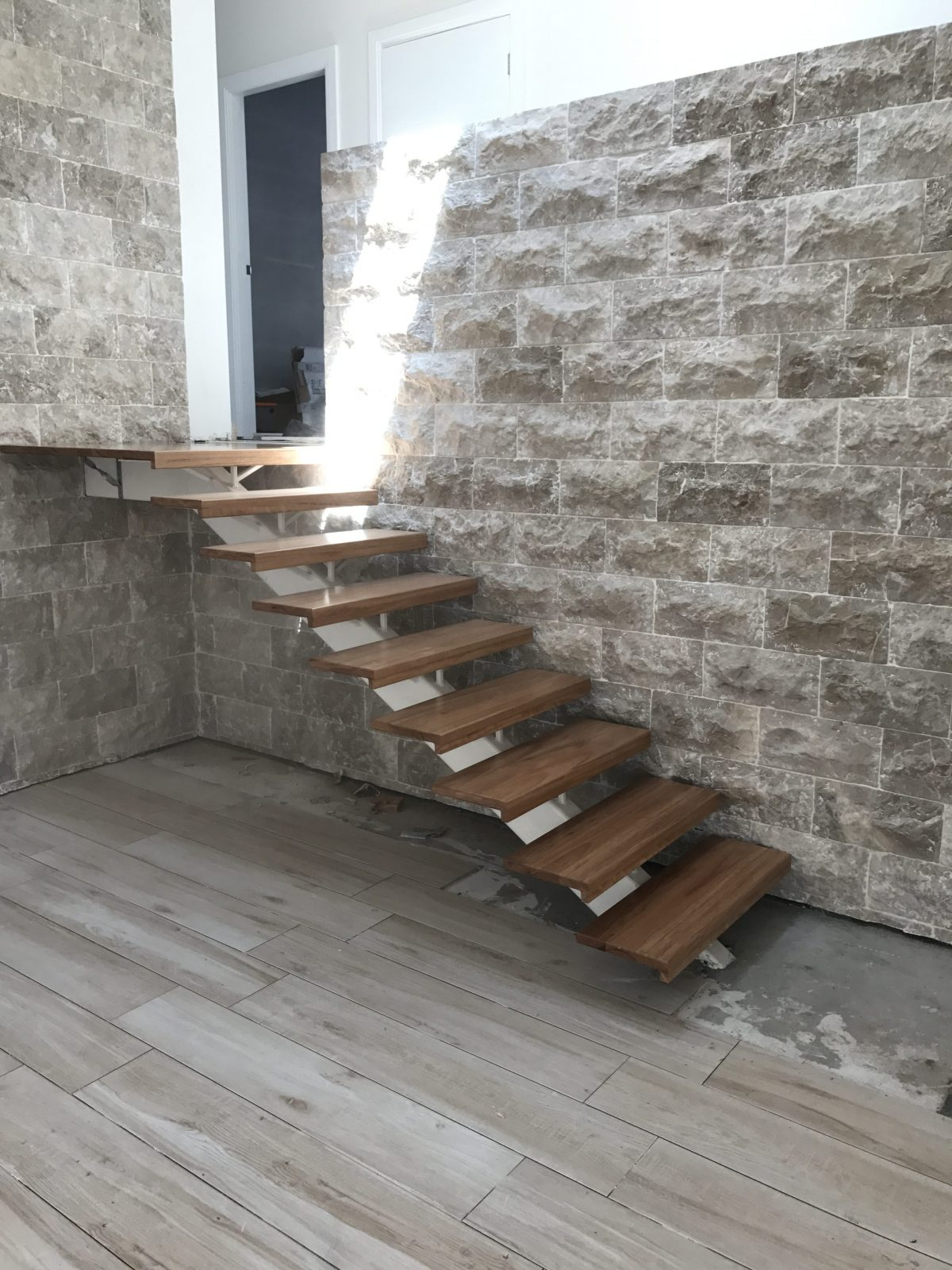 full side view of staircase fitted with solid treads fitted to steel spine supplied and installed by Timber Floors Pty Ltd