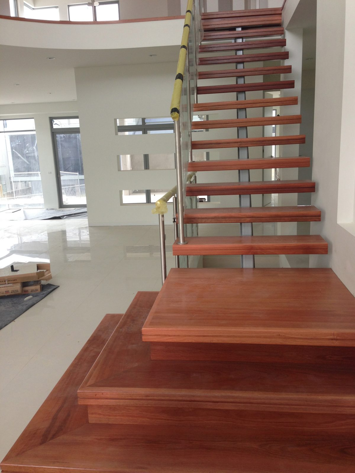 Solid treads with bespoke platform first 3 steps to create a stunning look to this metal spine staircase supplied and installed by Timber Floors Pty Ltd