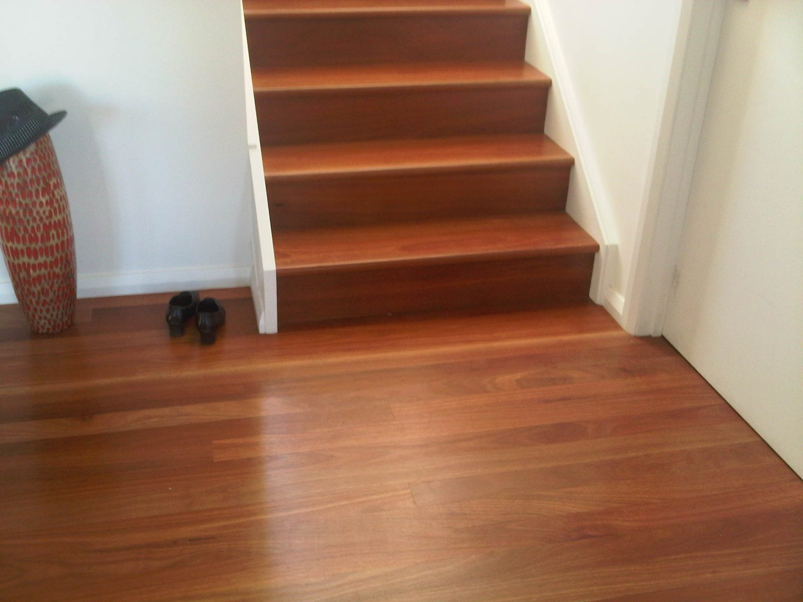 Solid hardwood Red Gum treads and risers wrapped to concrete formed staircase with matching solid timber flooring over concrete slab supplied and installed by Timber Floors Pty Ltd
